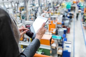 Person with ipad overlooking manufacturing facility