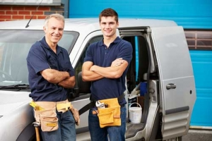 Two contractors standing next to a work van