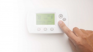 Picture of a hand adjusting a thermostat.