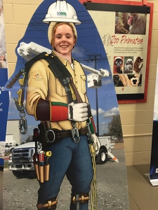 girl standing with a linemen cutout at Dakota Electric's member appreciation event at the Minnesota Zoo.