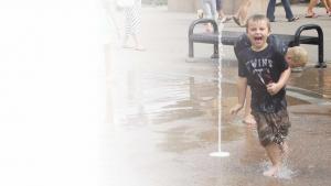 Child running through the sprinkler at Minnesota Zoo