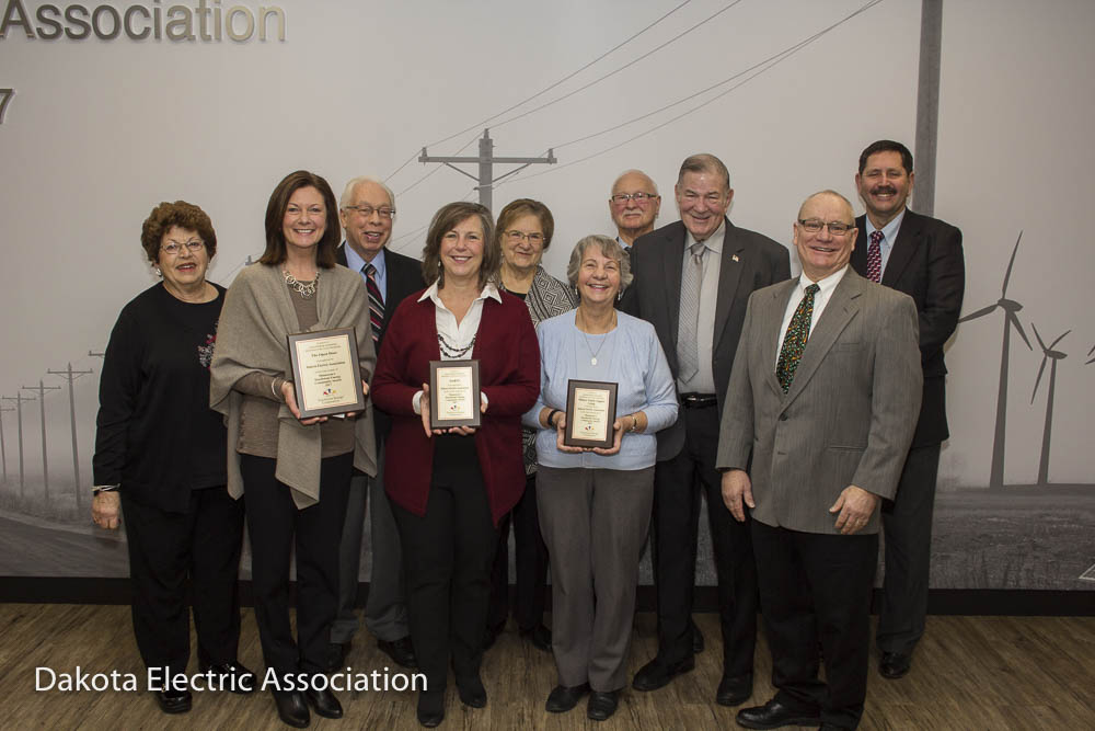 Touchstone energy winners holding their plaques with Dakota Electric board members.
