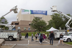 The main entrance of Zoo with bucket trucks holding welcome banner.
