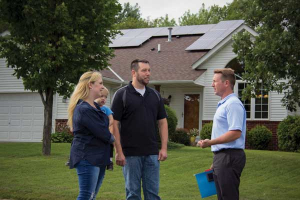 Young couple, members of Dakota Electric, stand outside their home after just installing rooftop solar panels.