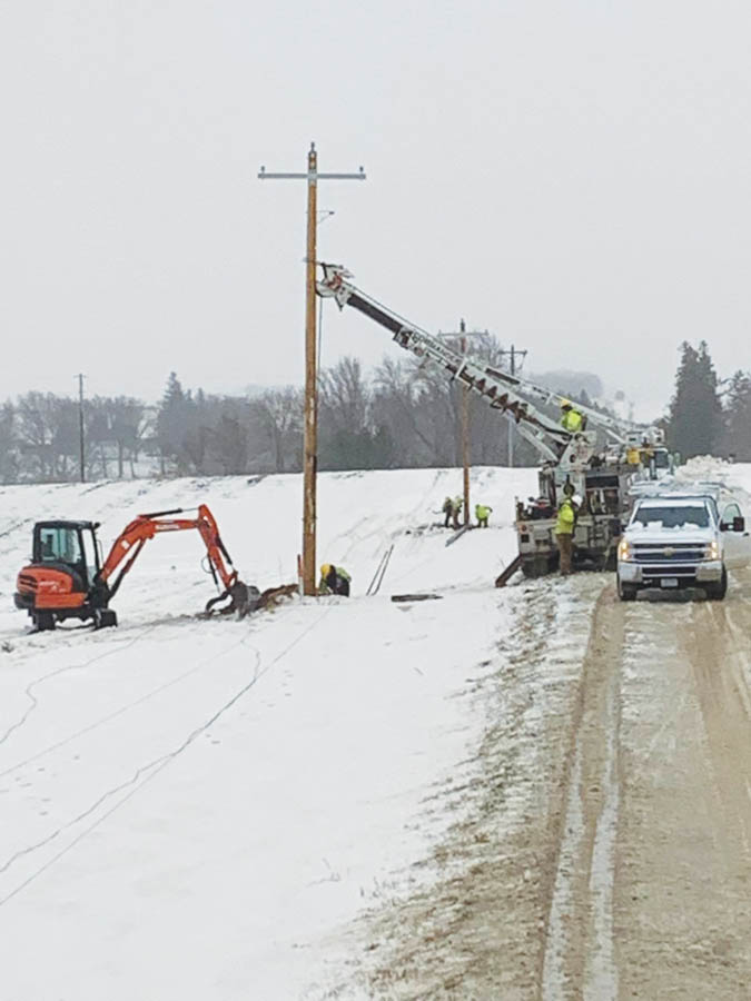 crews setting pole in snow