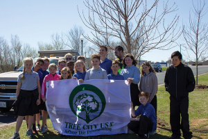 Group of kids holding tree planting banner