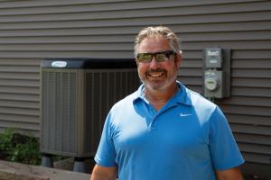 Jeff Neuman displays air source heat pump