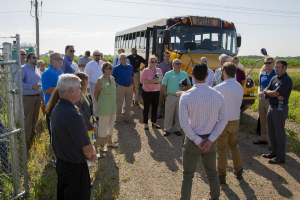 A crowd listening to a man while standing near an electric school bus.