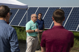 A man speaking to people with solar panels in the background.