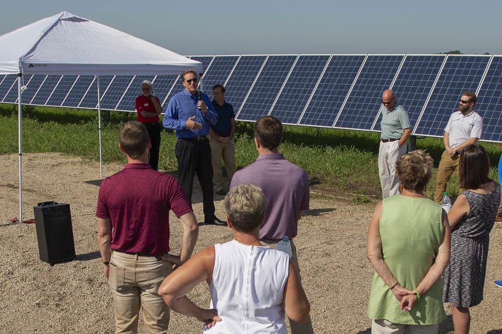 person speaking to crowd at solar panel site