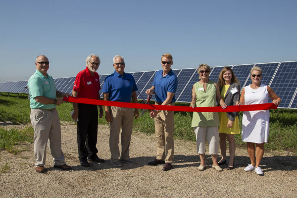 peopel cutting a ribbon at a solar panel site