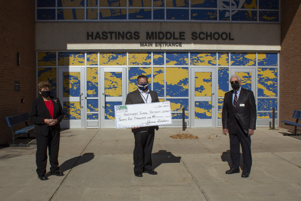 three people posing with a large check