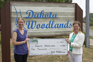 two people holding large check